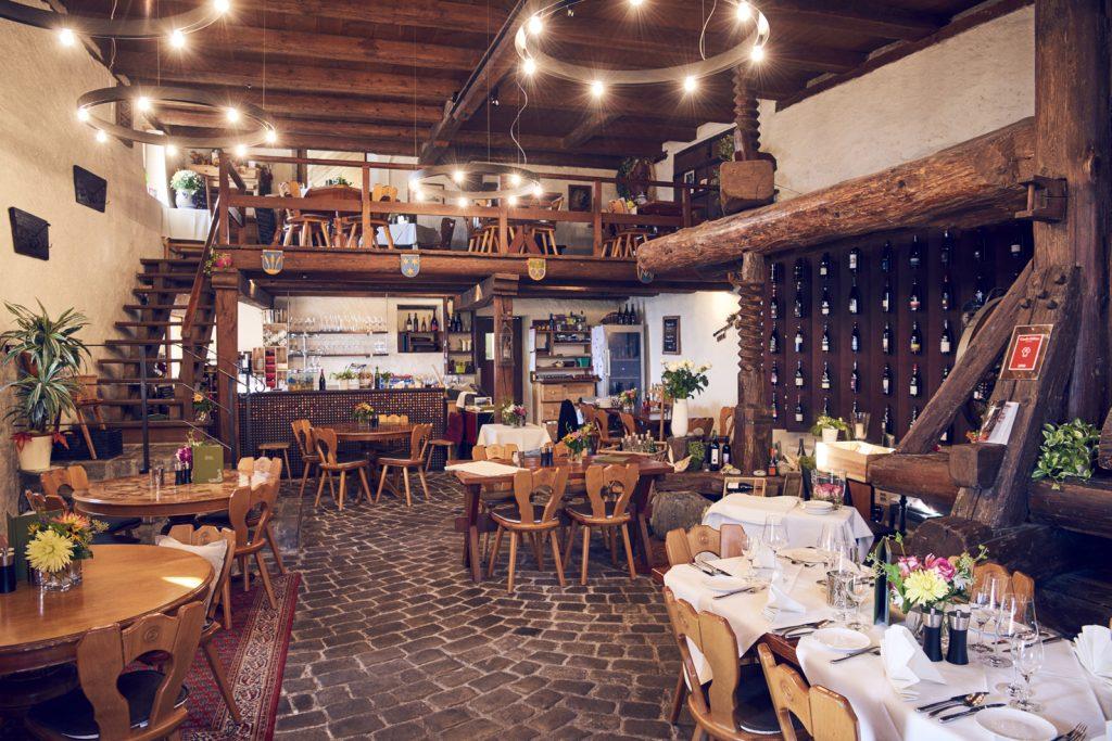 Die gepflästerte Weinwirtschaft. Rechts eine historische Baumpresse aus dem Jahr 1722. Dahinter eine drei Meter hohe Weinwand, von hinten subtil gekühlt,  mit Platz für über 1000 Flaschen. (Foto: Gian Marco Castelberg)